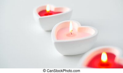 heart shaped candles burning in st valentines day -...