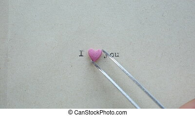Heart shaped candy with loving words on the paper made with...