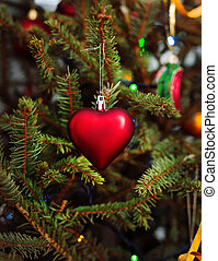 heart shaped christmas toy on spruce branch