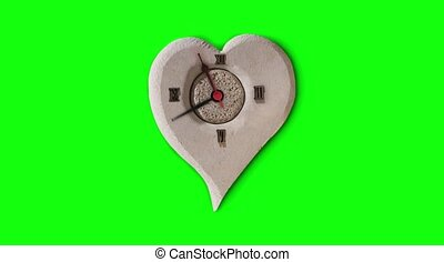 Heart-shaped clock on a green background