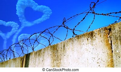 Heart-shaped cloud in the sky behind barbed wire fence on a...