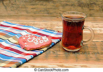 heart shaped cookie with tea in glass mug