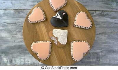 Heart-shaped cookies coated with glaze. Pink, black and white homemade heart shape cookies on wooden background. Happy Valentines Day.