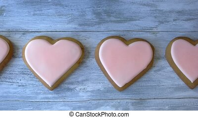 Heart shaped cookies with pink icing. Row of fresh desserts...
