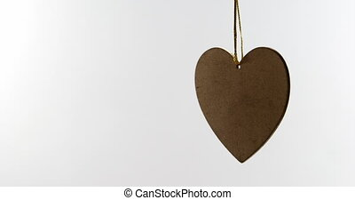 Heart shaped decoration hanging in mid air. Pendant tied to string 4k