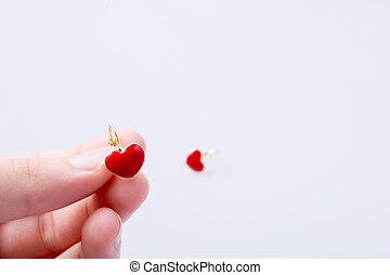 Heart shaped earring in hand on white