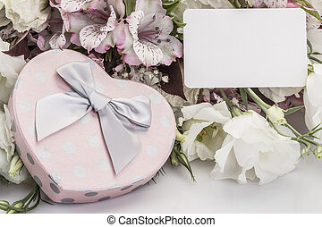 Heart shaped gift box and flowers with a name tag