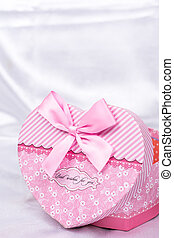 Heart shaped gift box over white satin