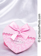 Heart shaped gift box with bow over white satin