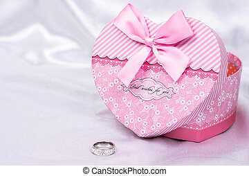 Heart shaped gift box with wedding ring over white satin