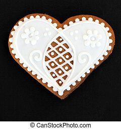 heart shaped gingerbread cookie isolated on black