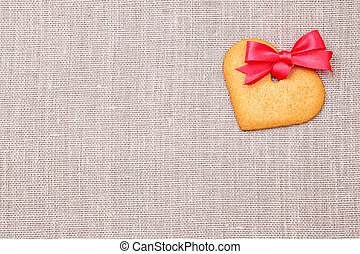 Heart shaped gingerbread cookie over linen cloth