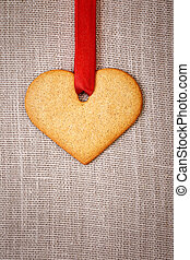 Heart shaped gingerbread cookie with red ribbon