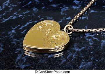 Heart shaped gold locket. - Heart shaped gold locket against...