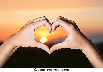 Heart shaped hands with sunrise