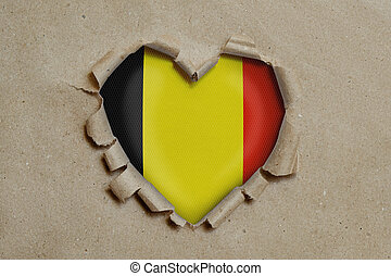 Heart shaped hole torn through paper, showing Belgian flag