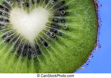 Closeup of a heart shaped kiwi slice covered in water bubbles