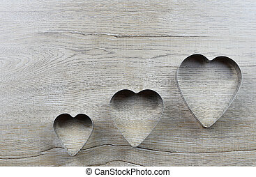 Heart-shaped mold rests on a wooden table and has a copy space.