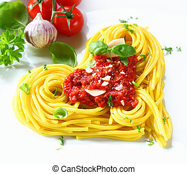 Cooked spaghetti arranged in a heart shape topped with tomato sauce and fresh basil