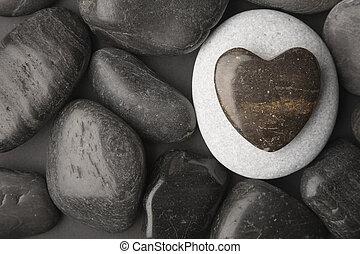 Heart shaped pebble framed on a dark pebble background