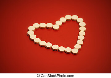 Heart shaped pills on red background