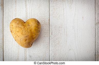 Heart Shaped Potato - Heart shaped potato on white wooden...