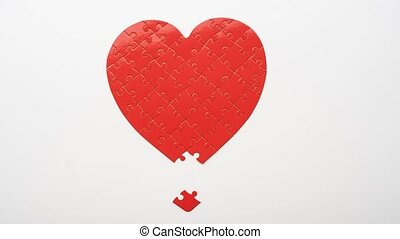 Top view of red heart shaped jigsaw puzzle matching from pieces on white background, timelapse