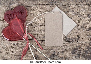 heart shaped red candies on wooden table with labels