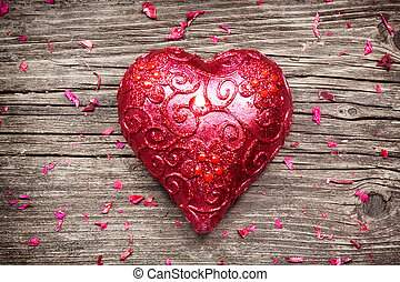 Heart shaped red candle with flower petals on old wooden table