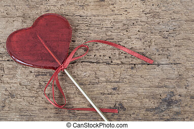 heart shaped red candy on wooden background with copy space