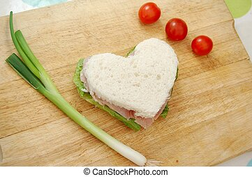 Heart shaped sandwich with spring onion and cherry tomatoes