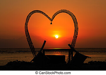 Heart shaped silhouette on beach at sunset