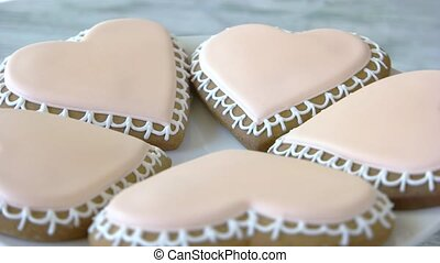 Heart-shaped sugar cookies. Heart-shaped sweets coated in pink frosting.