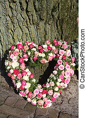 A sympathy flower arrangement, heart shaped and made of pink roses