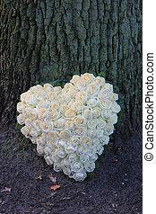 A sympathy flower arrangement near a tree in the shape on an heart