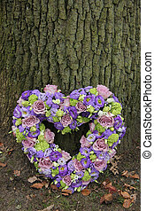 Heart shaped sympathy flowers in different shades of purple