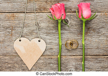 Heart shaped tag, wedding rings and roses