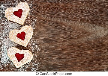 Heart shaped Valentines Day cookies side border with powdered sugar over a rustic wood background