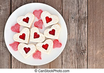 Heart shaped Valentines Day cookies with jam and candies on a white plate over a rustic wood background