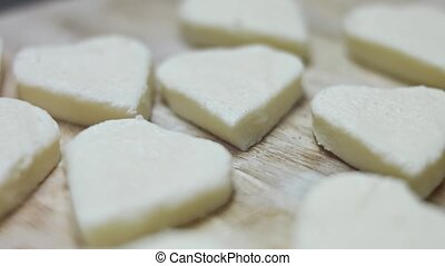 Heart shapes of mozzarella cheese on a wooden cutting board. 4k video. Preparing food for Valentine's Day. Close-up