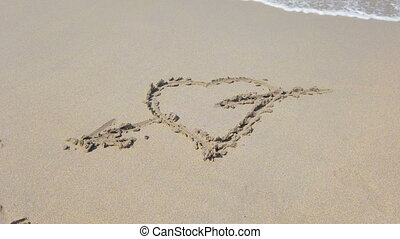 Heart shapewith arrow on sand that wiped off by sea wave -...