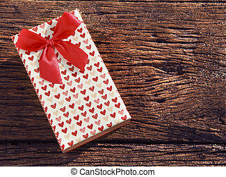 heart spot present gift box with red ribbon on old wood textured with copy space use for gift event in cristmas valentine and new years greeting