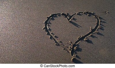 Heart symbol drawn by hand on sand. Top view