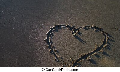 Heart symbol drawn by hand on sand washes away in wave. Slow motion