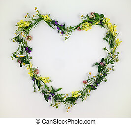 Heart symbol made of flowers and leaves on white background
