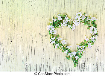 Heart symbol made of flowers on wooden background.