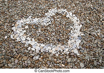 heart symbol made of pebbles on the beach