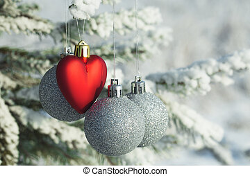 Heart toy with silver balls on a pine branch in the snowy forest.