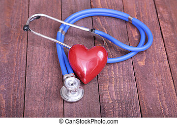 Heart with a stethoscope, isolated on wooden background