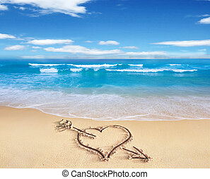 Heart with arrow, as love sign, drawn on the beach shore, with the see and sky in the background.
